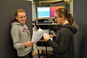 Zwei Schülerinnen halten Texte und lesen vor einem Mikrophon